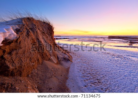 sunset on the dunes of the Baltic Sea to the snow-covered river in the foreground - stock photo