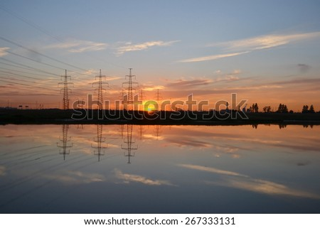 Sunset on the lake and transmission power line. - stock photo