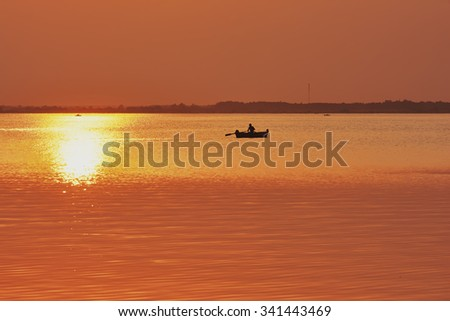 Sunset on the lake. Boat with fisherman at sunny track on water