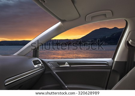 sunset on the lake viewed from inside a car