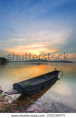 Sunset on the lake with a boat  - stock photo