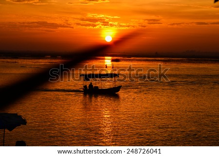 sunset on the lake with boat - stock photo