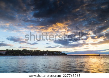 Sunset on the Mediterranean sea with green top white lighthouse and trees and buildings on the St. Nicholas island in the cloudy background near Porec in Croatia - stock photo