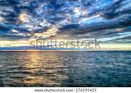 Sunset on the Mediterranean sea with red steel lookout on eyot and green top white lighthouse in the cloudy background near Porec in Croatia - stock photo