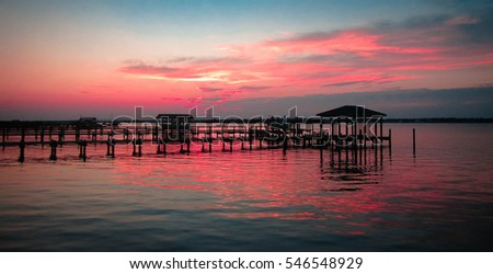Sunset on the ocean with pink skies and silhouette docks