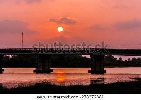 sunset on the river and the bridge - stock photo