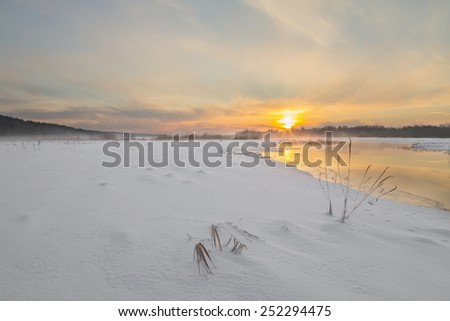 Sunset on the river in the winter in frosty weather with fog - stock photo