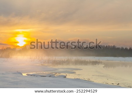 Sunset on the river in the winter in frosty weather with fog. Bright sunny winter day at the river - stock photo