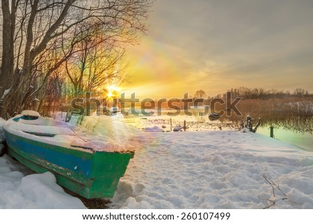Sunset on the river with the boat in the winter with fog. Sun beams. Bright clear day. - stock photo