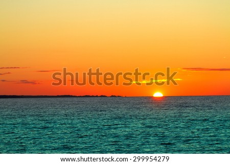 sunset on the sea. red and orange sun and blue water - stock photo