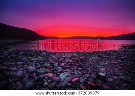 Sunset on the stone coast - stock photo