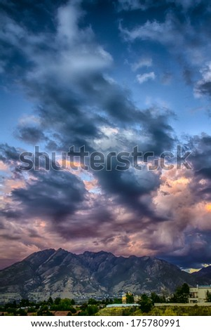 Sunset on the thunder clouds over the Wasatch mountains as seen from the Salt Lake City Valley in Utah USA/Rumble Over the Wasatch - stock photo