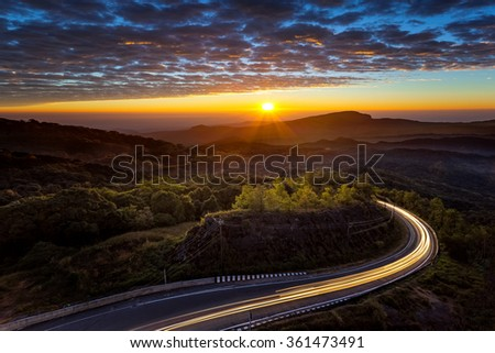 Sunset on the top mountain and road at front - stock photo