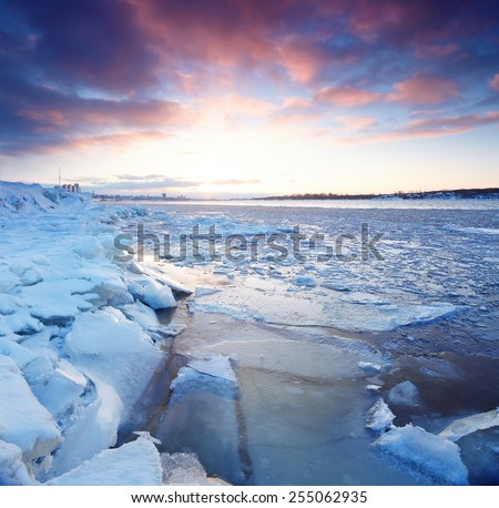 Sunset on the winter river with sharp focus of foreground