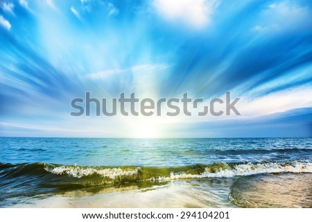 Sunset on tropical beach and blue sea, white clouds on background - stock photo