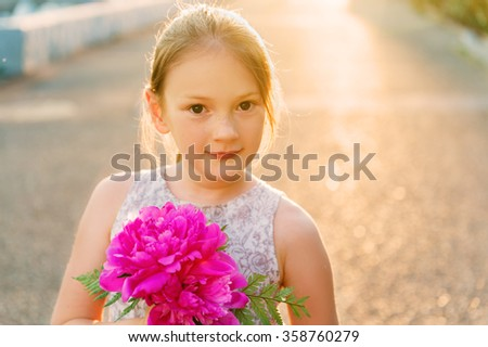 Sunset outdoor portrait of a cute little girl with small bouquet of bright pink peonies - stock photo