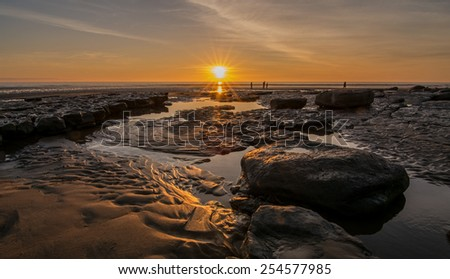 Sunset over a beach in South Wales, reflecting in rivulets of water, with people silhouetted on the shore - stock photo