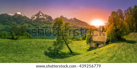Sunset over a glade in the Alps mountains - Idyllic spring panorama with the sun setting down over the Alps mountains, Walensee lake and a green glade, near the Amden municipality, Switzerland. - stock photo