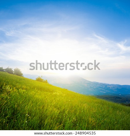 sunset over a green hills - stock photo