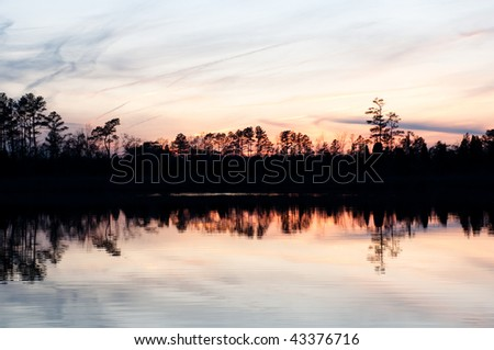 sunset over a lake in the woods - stock photo