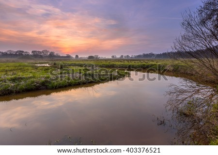 Sunset over a lowland meander in the Regge river, Twente Netherlands. A meander forms when moving water in a stream erodes the outer banks, the inner part of the river deposits silt.