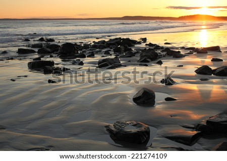 Sunset over a remote beach - stock photo