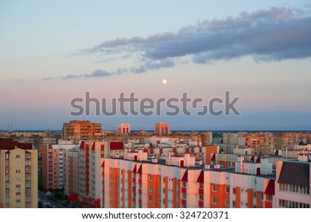 Sunset over a residential apartment houses with moon - stock photo