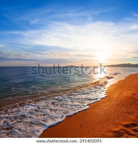 sunset over a sea coast - stock photo