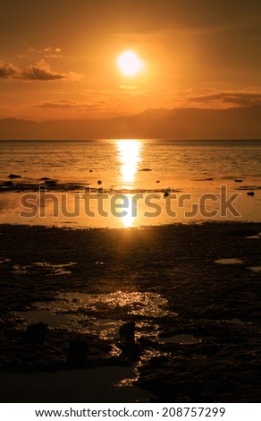 Sunset over a tropical ocean - stock photo