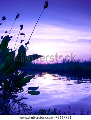 sunset over an green steppe and blue lake - stock photo