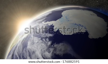 Sunset over Antarctica region on planet Earth viewed from space with Moon and stars in the background. Elements of this image furnished by NASA.