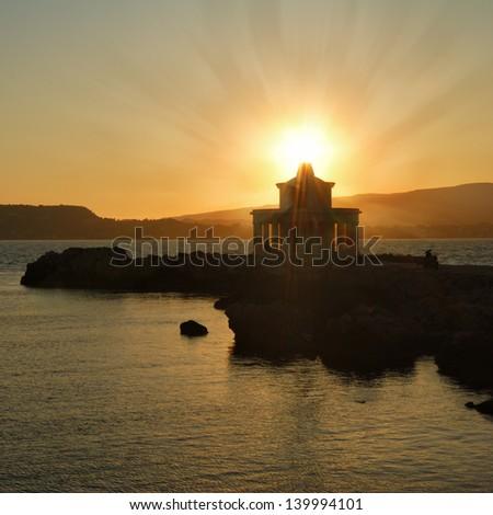 Sunset over Argostoli Lighthouse on Cephalonia Island - stock photo
