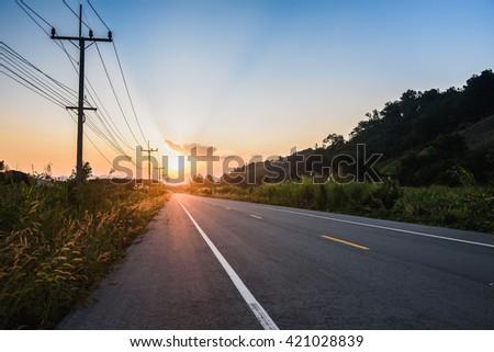 sunset over asphalt road - stock photo