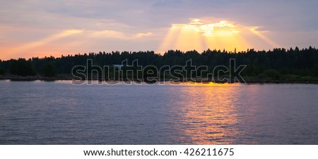 Sunset over Baltic Sea coast, sunbeams goes trough stormy clouds. Gulf of Finland - stock photo