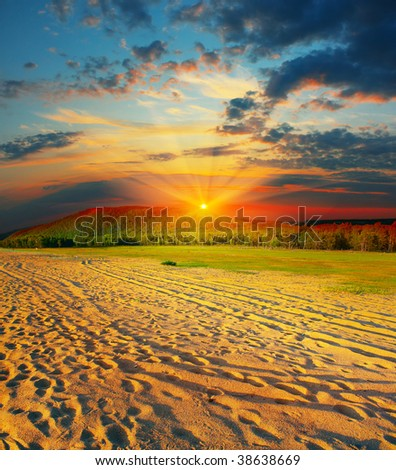 Sunset over beach with sand - stock photo