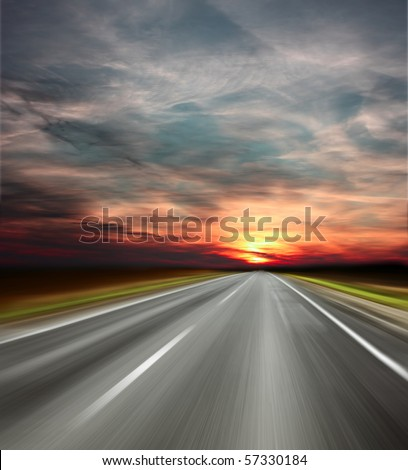 Sunset over blurred asphalt road - stock photo