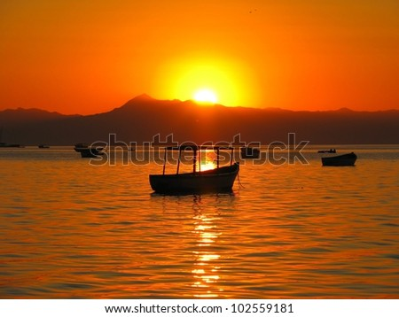 Sunset over boats on Lake Malawi, Cape Maclear, Malawi - stock photo