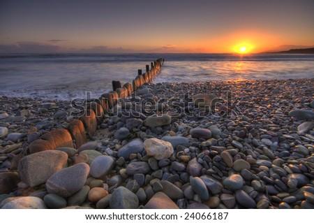 Sunset over breakwater - stock photo