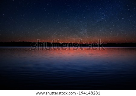 Sunset over Calm Lake with Real Stars in Dark Sky - stock photo