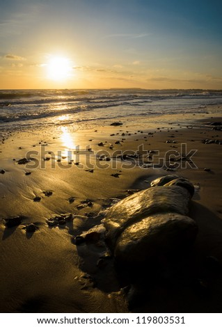 Sunset over Christchurch Bay with reflection on the sandy beach near Barton on Sea - stock photo