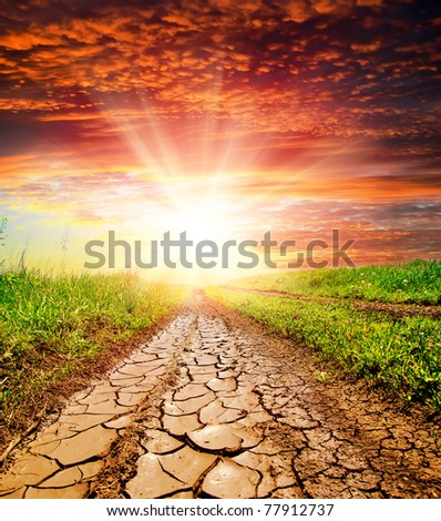 sunset over cracked rural road in green grass and cloudy sky - stock photo