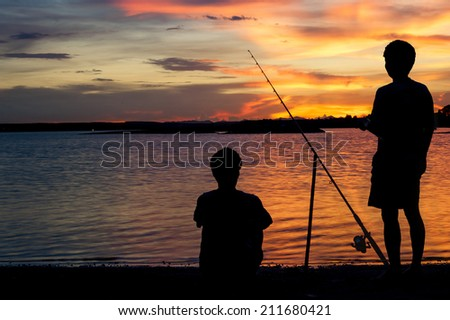 Sunset over dam with Fisherman silhouette and different shades of pink and orange - stock photo
