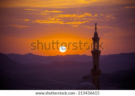 Sunset over desert with muslim mosque in the foreground. Focus on distant mountains - stock photo