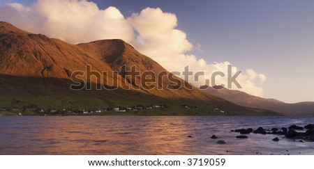 Sunset over distant mountains, fluffy white clouds are tinged with orange and frame the mountain slopes. Calm water and silhouetted rocks form the foreground - stock photo