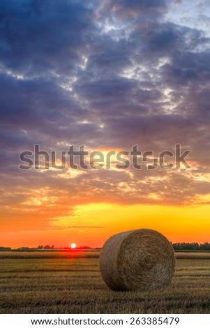 Sunset over farm field with hay bales in Hungary - stock photo