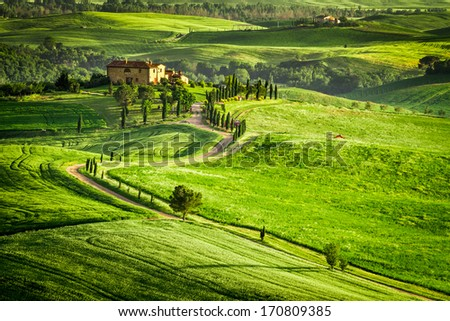 Sunset over farmhouse in Tuscany located on a hill - stock photo