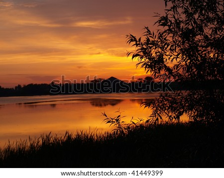 Sunset over lake in mountains - stock photo