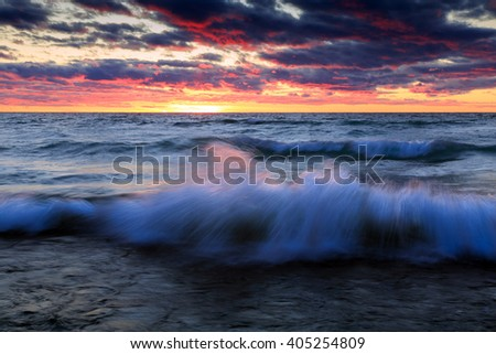 Sunset over Lake Michigan with gale winds create large waves crashing on to the beach. - stock photo