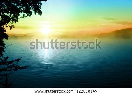 Sunset Over Lake Tree Fog Sky Landscape Background - stock photo