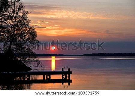 Sunset over lake with silhouette of jetty - stock photo